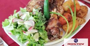 Цял бавно печен свински джолан със сос барбекю, гарниран с печени картофки и моркови и свежа зелена салата